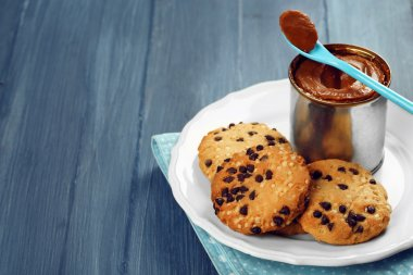 Can of boiled condensed milk with spoon and cookies