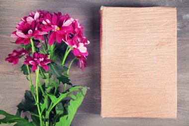 Bouquet of flowers with book on wooden table, top view