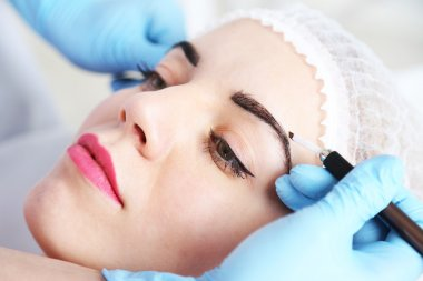 Cosmetologist applying permanent make up