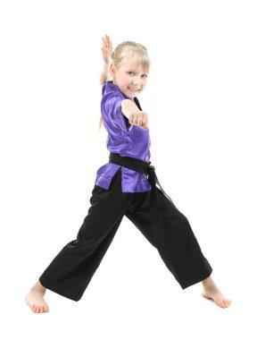 Little girl in kimono doing exercises
