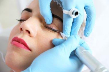 Cosmetologist applying permanent make