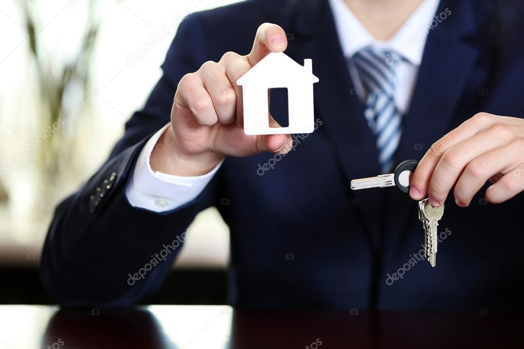Businessman with keys in his hand in office on blurred background