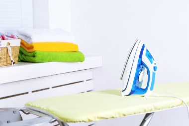 Iron on ironing board on light home interior background