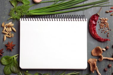 Open recipe book with fresh herbs