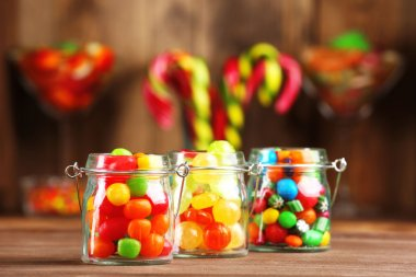 Colorful candies in jars on table in shop stock vector