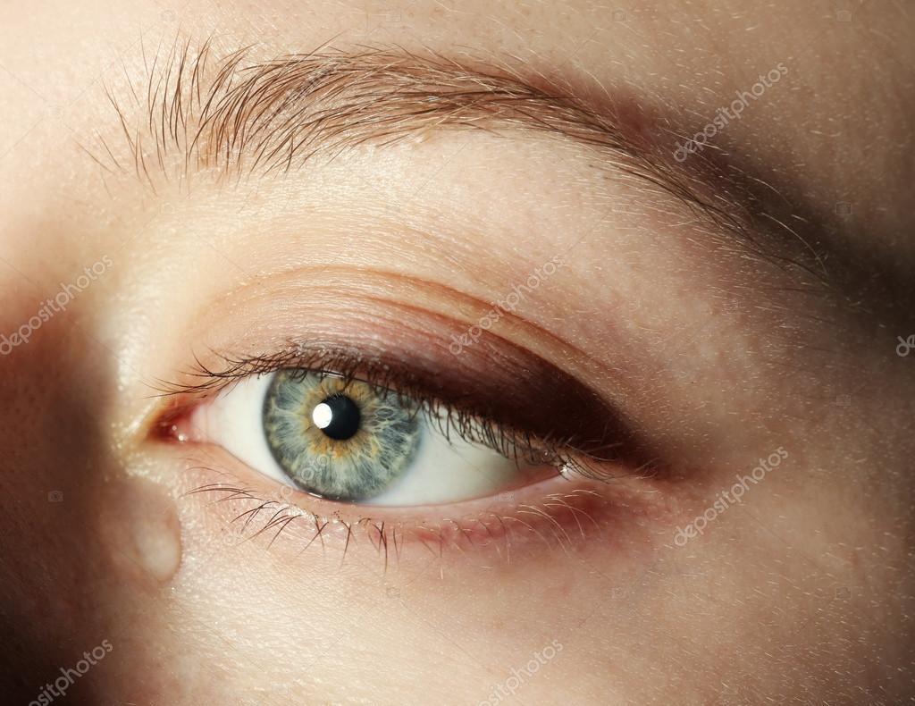 Auge der jungen Frau mit Tränen tropfen aus nächster Nähe