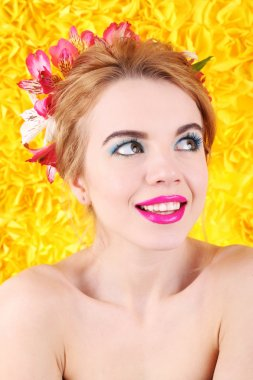 Portrait of young woman with flowers in hair on bright yellow background