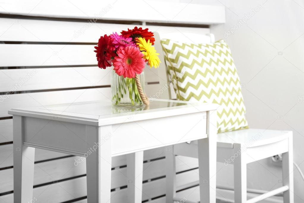modern interieur met witte stoel en kussen in de buurt van salontafel met kleurrijke gerbera