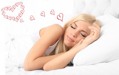 Beautiful young woman dreaming about love while sleeping