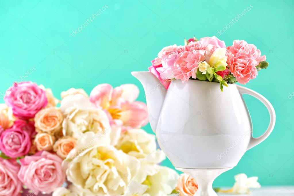 34720f21b5 Kompozíció szép tavaszi virágok a teáskanna világoskék háttér– stock kép