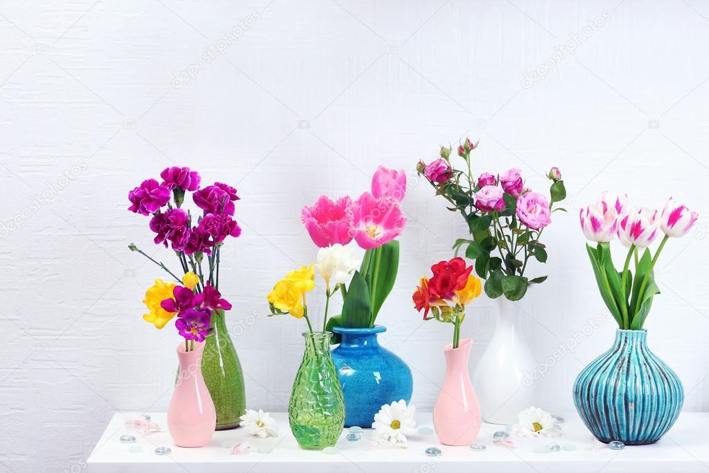 Beautiful Composition With Different Flowers In Vases On Wall