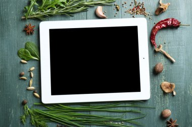 Digital tablet with fresh herbs and spices on wooden background