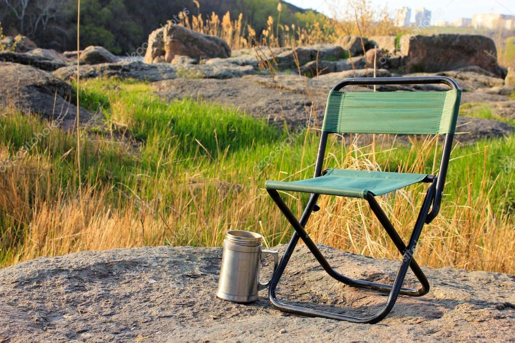 Camp chair and thermos cup on nature background