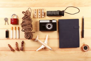 Travel gear on wooden table, top view