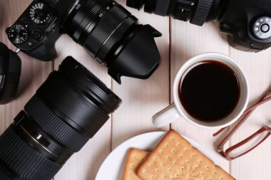 Modern cameras with glasses, cup of coffee and cookies on wooden table, top view