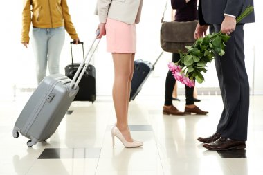 Legs of young couple with baggage and flowers in airport