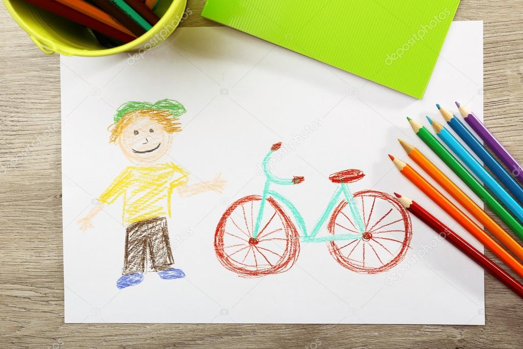 kids drawing on white sheet of paper on wooden table top view stock photo