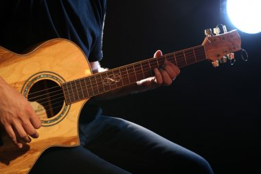 Young man playing on acoustic guitar on dark background