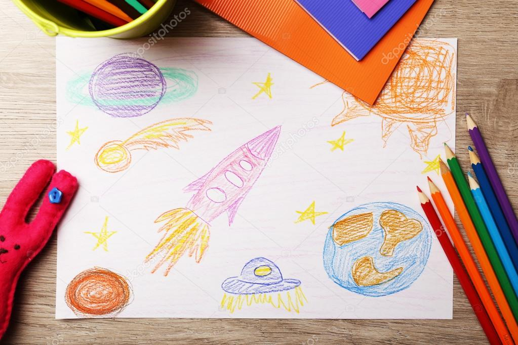 Kids drawing on white sheet of paper on wooden table, top view ...