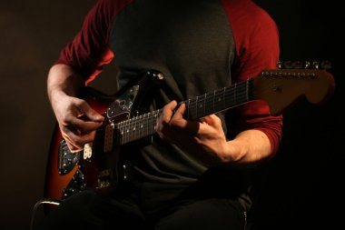 Young man playing on electric guitar on dark background