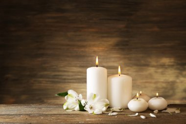 Candles with flowers on wooden background
