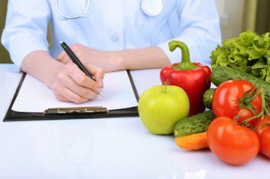 Nutritionist doctor writing  diet plan in office