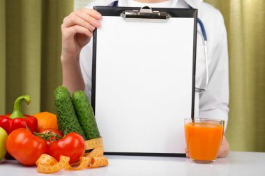 Nutritionist doctor with clipboard for diet plan in office