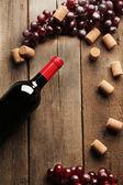 Skleněná láhev vína s zátky a hrozny na dřevěný stůl pozadí