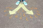 Fotografie Frauenfüße auf Asphalt mit Zeichenpfeilen, im Freien