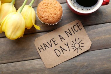 Cup of coffee with fresh cupcake, tulips and Have A Nice Day massage on wooden background