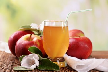 Glass of apple juice and apples on wooden table, on nature background