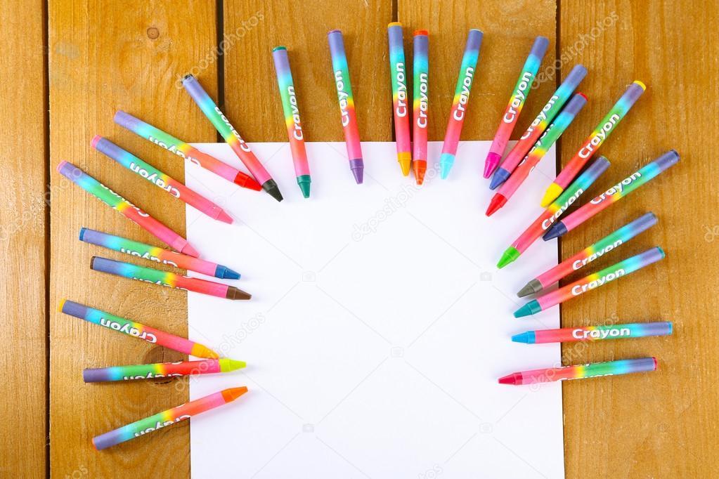 Crayones pasteles coloridos con hoja blanca de papel en mesa de ...
