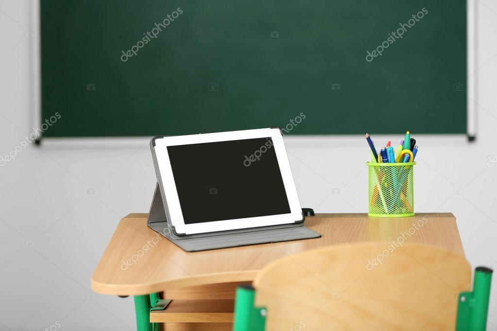 Bureau en bois avec papeterie et tablette en classe sur fond noir
