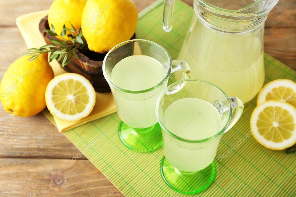Still life with lemon juice and sliced lemons on color mat, closeup