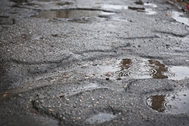 Holes with puddles on damaged asphalt background