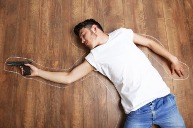 Crime scene simulation, young man lying with gun on floor
