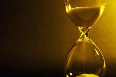 Hourglass on dark yellow background