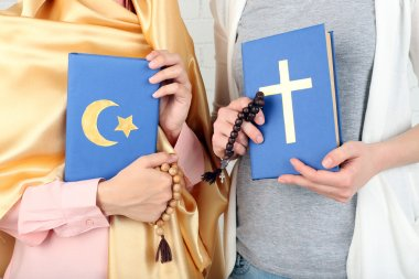 Two friends holding books with religions symbols