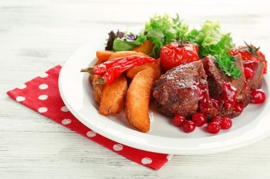 Tasty roasted meat with cranberry sauce and roasted vegetables