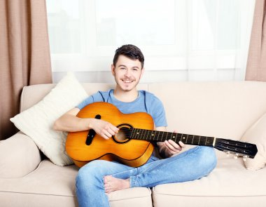 Young man with guitar on sofa in room