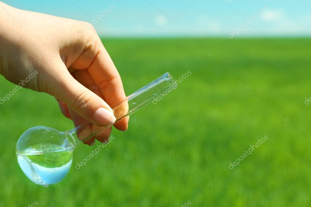 Female hand with test tube over natural background