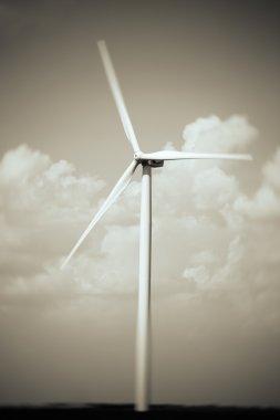 Windmill in field on sky background