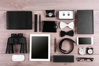 Set of black and white accessories on wooden table, top view