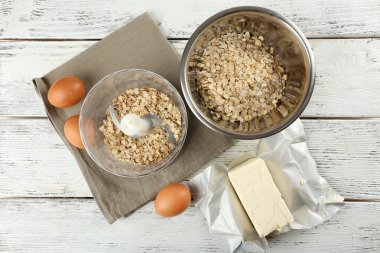 Ingredients for oatmeal cookies on wooden table, top view