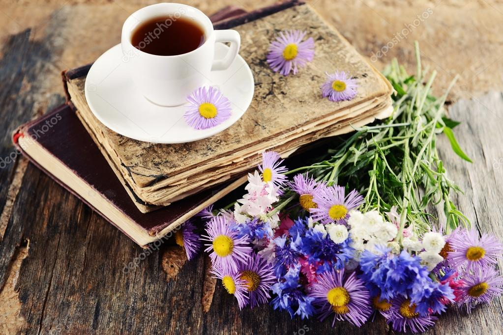 Old books with beautiful flowers and cup of tea on wooden ...