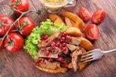 Hovězí maso s brusinkovou omáčkou, opečené bramborové plátky a buchta na prkénko, na dřevěné pozadí