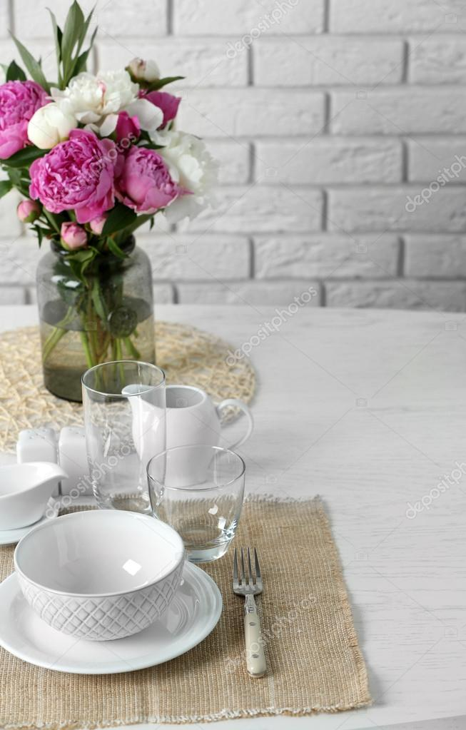 Beautiful table setting with flowers in vase on brick wall background u2014 Photo by belchonock & Beautiful table setting with flowers in vase on brick wall ...