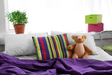 Comfortable bed with teddy bear in bedroom