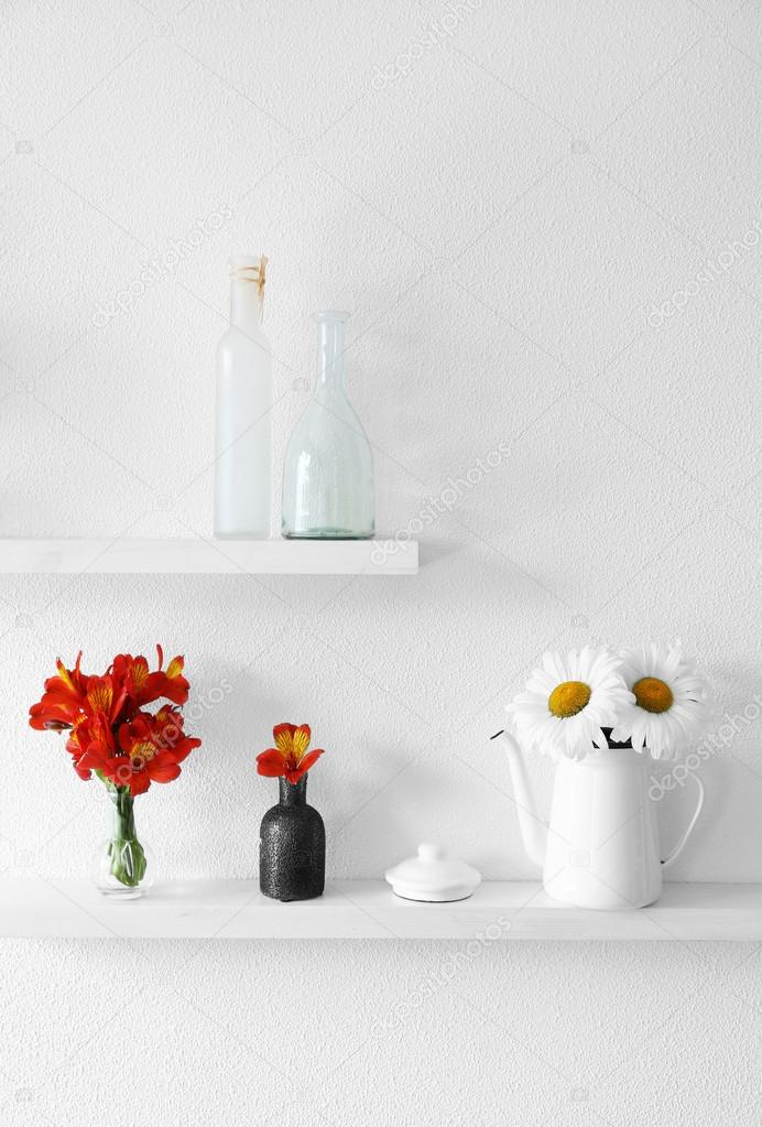 Decorative Vases With Flowers On Wooden Shelf On White Wallpaper