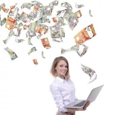 Young business woman with laptop in the rain of money, isolated on white